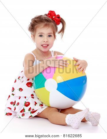 beautiful girl sitting on the floor with a large striped inflata