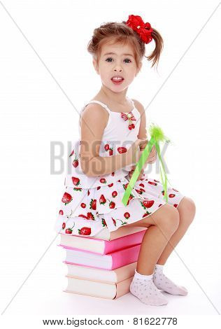 beautiful little girl sitting on colorful books in hand wand.