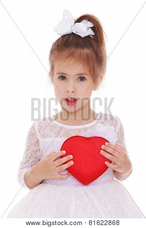 Delicate and charming little girl close to her heart-shaped box.