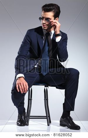 Attractive business man sitting on a stool, looking down while taking off his sunglasses.