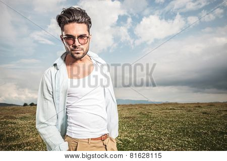 Young attactive man posing outside, on a field with flowers, holding his hands in pockets.