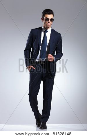 Full body picture of a young elegant business man pulling his jacket while holding one hand in his pocket.