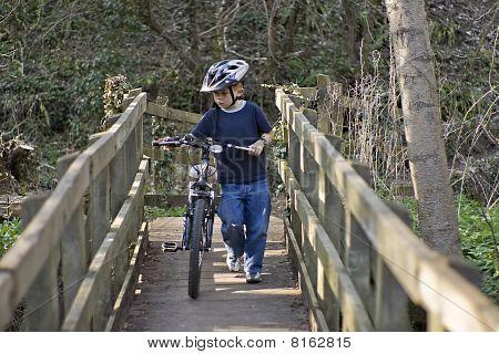 A Young Six Year Old Boy Pushing His Bike Across A Bridge