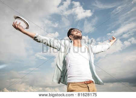 Happy young man looking up to the sky holding both hands in the air, enjoying the sun.