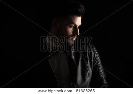 Attractive business man looking down to his side on dark studio background.