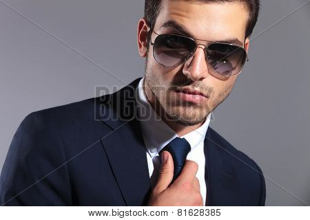 Close up image of a young elegant business man wearing sunglasses, fixing his tie.