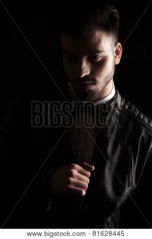 Close up picture of a young business man looking down while fixing his jacket, on dark studio background.
