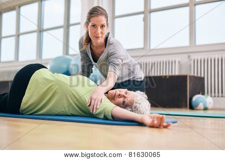 Trainer Helping Senior Woman In Her Stretching Workout