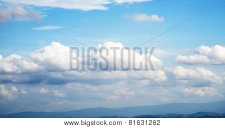 Bright blue sky with many drifting clouds