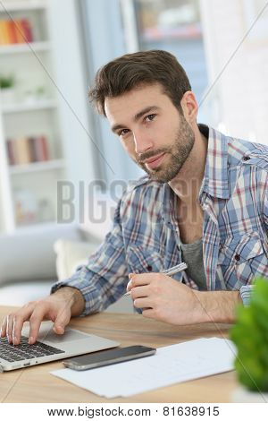 Man working from home with laptop and taking notes