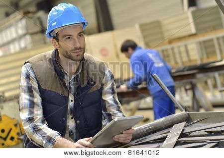 Engineer in metallurgical factory using tablet