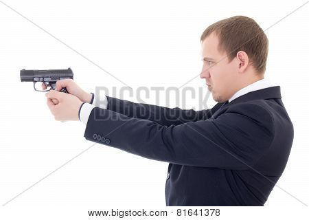 Side View Of Man In Business Suit Shooting With Gun Isolated On White