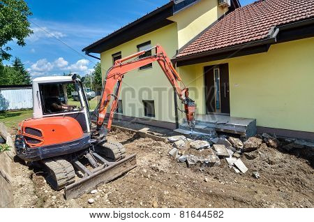 A Crusher Is Demolishing A House
