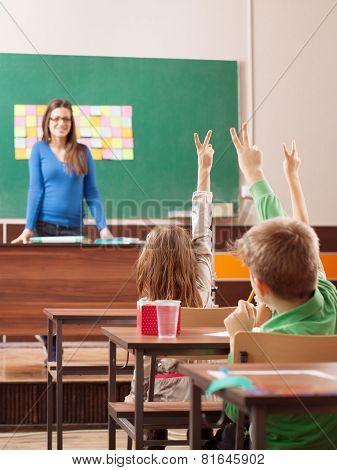Children In Elementary School Are Raised Hand In Classroom