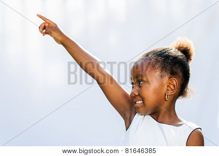 African Girl Pointing And Looking At Corner.