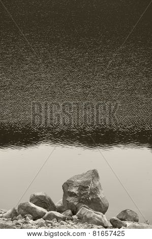 Scottish Landscape With Loch And Rocks On A Rainy Day