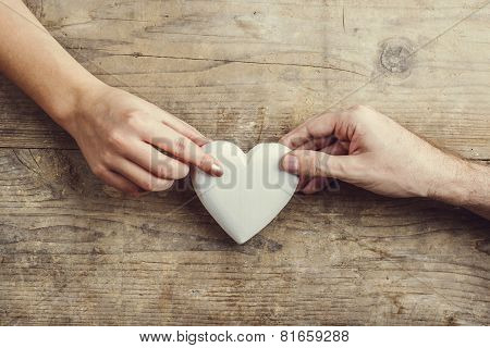 Hands of man and woman connected through a heart.