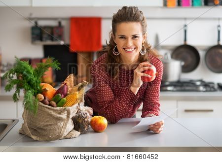 Portrait Of Happy Young Housewife Holding Grocery Shopping Check