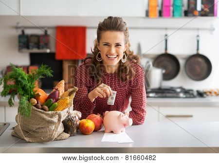 Portrait Of Happy Young Housewife Putting Money Into Piggy Bank