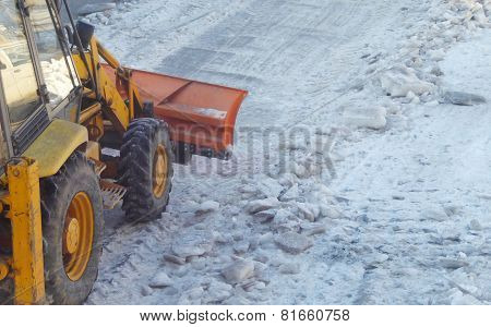 Bulldozer cleaning the road from ice