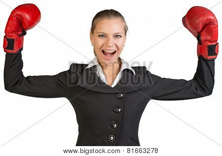 Businesswoman wearing boxing gloves standing in victory pose, looking at camera, shouting