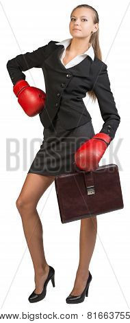 Businesswoman wearing boxing gloves standing akimbo