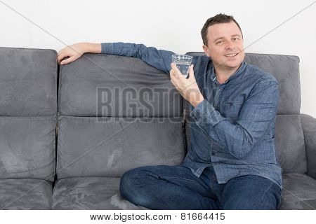 Man Holding A Glass Of Water While He Is Sat On The Couch