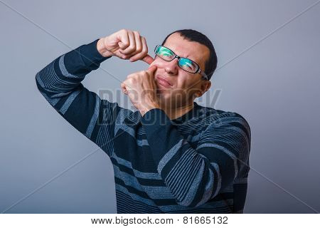 European-looking male of about thirty brunet squeezing a pimple