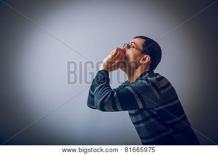 European-looking male put his hands to mouth, shouting