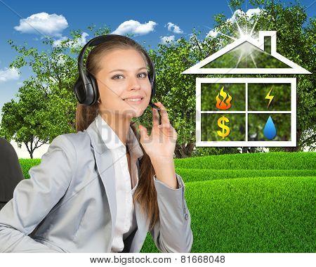 Businesswoman in headset, symbols of public utilities beside