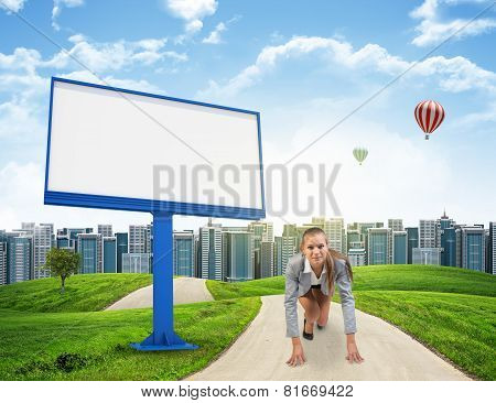 Businesswoman in running start pose on the road