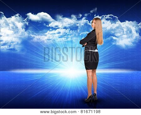 Businesswoman standing against blue landscape with rising sun