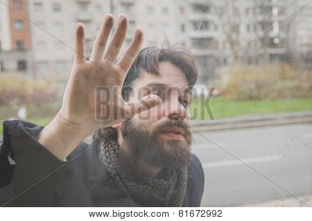 Young Handsome Bearded Man Posing Behind A Glass