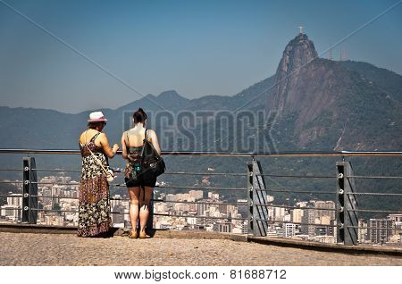 Two women watching the skyline of Rio de Janeiro from the lookout point on the Sugarloaf Mountain