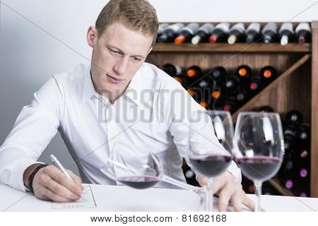 Male Winemaker Examining A Wine Glass.