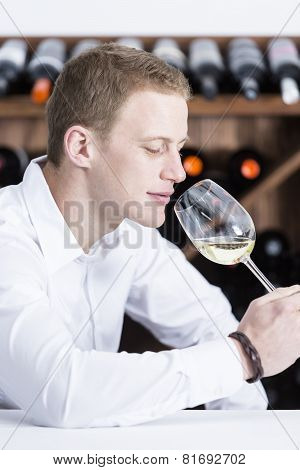 Man Smelling A White Wineglass