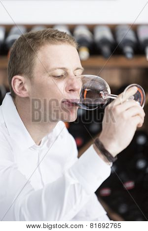 Man Tasting A Red Wine Glass .