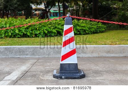 Red-white Traffic Cone And Chain On Street