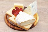 stock photo of brie cheese  - edam parmesan and brie cheese on wooden platter over wooden table - JPG