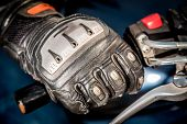 image of motorcycle  - Human hand in a Motorcycle Racing Gloves holds a motorcycle throttle control - JPG