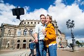 image of selfie  - Tourist couple at Semperoper in Dresden taking selfie with phone on stick - JPG