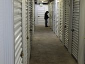 pic of self-storage  - A woman stands at the end of a row of self storage lockers - JPG