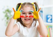 pic of finger-painting  - cute kid girl have fun painting her hands and face - JPG