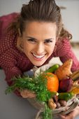 stock photo of local shop  - Portrait of happy young housewife with shopping bag of fresh vegetables from local market - JPG