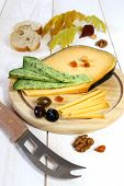 picture of cheese platter  - Cheese platter: solid cheese Provencal olives walnuts and autumn leaves