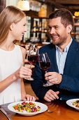 foto of evening gown  - Beautiful young loving couple toasting with red wine and smiling while sitting at the restaurant together - JPG