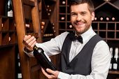 stock photo of liquor bottle  - Confident male sommelier holding wine bottle and smiling while standing near the wine shelf - JPG