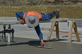 image of concrete pouring  - A builder uses a sawhorse and plank to position himself while floating off new concrete for a large building near Greymouth South Island New Zealand  - JPG