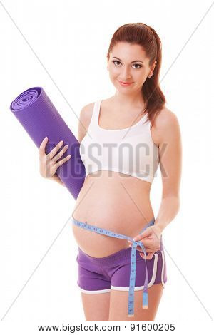 Beautiful pregnant woman with exercising mat and measure tape on the white background