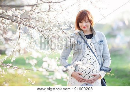 Fashion pregnant woman enjoying of the spring blooming
